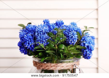 Blue bell flowers in glass vase on wooden background