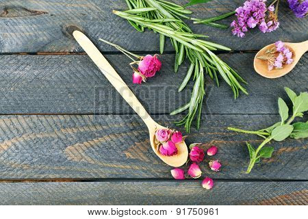 Green herbs and leaves on wooden  table, top view