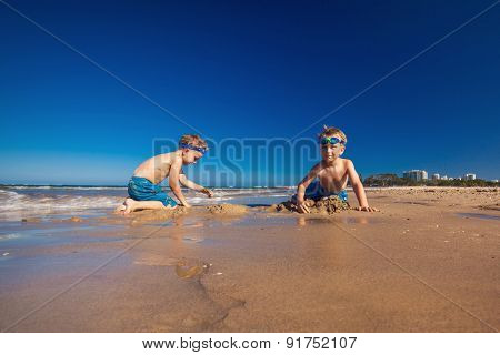 Two young boys playing on a beach with clean blue sky