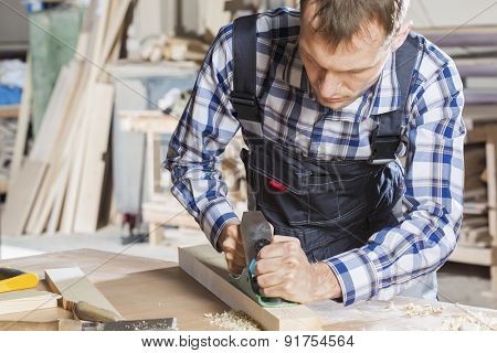 Carpenter working with plane in his studio