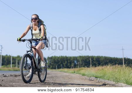 Young beautiful woman riding a bicycle on road