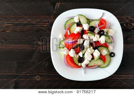 Greek Salad overhead view with dark wood background