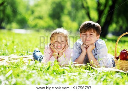 Sister and brother in the park reading a book
