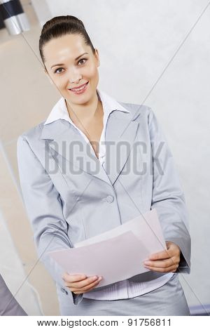 Young attractive businesswoman at meeting with documents in hands