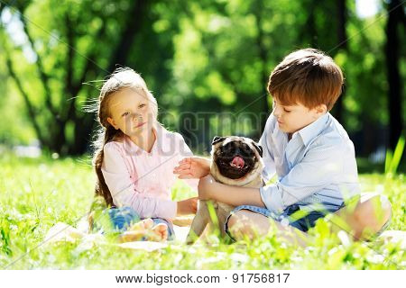 Adorable boy and girl in summer park with their dog