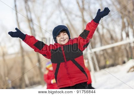 Little cute boy having fun in winter park