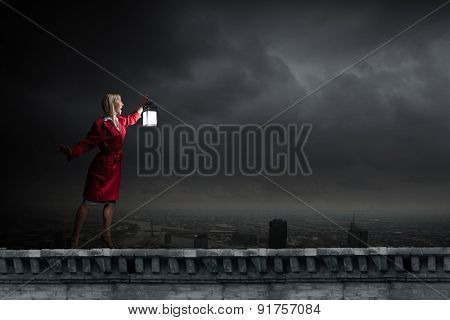 Young blond woman in red cloak with lantern walking in night