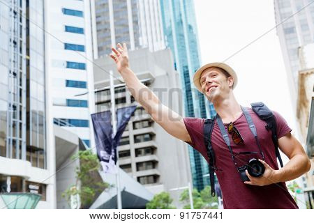 Male tourist calling for a taxi in the city