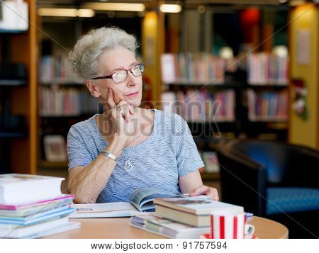 Elderly lady reading books in library