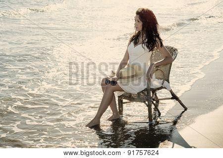 Girl Sitting On A Chair By The Sea