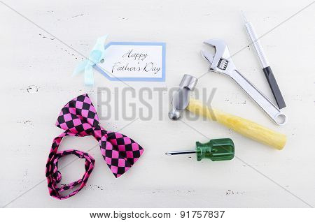 Happy Fathers Day Concept With Mens Tools And Pink Bow Tie.
