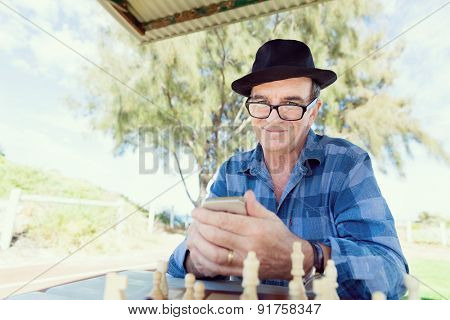 Portrait of an old man with his mobile phone outdoors