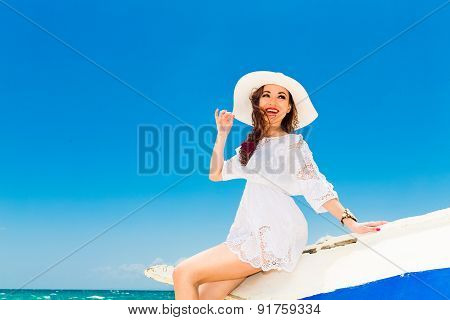 Happy Young Brunette In A White Straw Hat And White Dress Sitting On An Old Fishing Boat