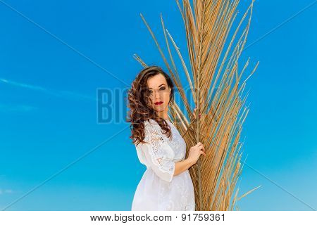 Young Brunette In White Dress Sianding With Palm Leaves On A Tropical Beach. Summer Vacation Concept
