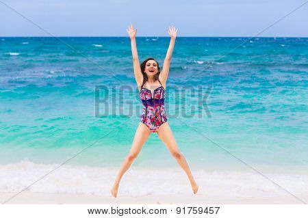 Happy Young Brunette In A Swimsuit On A Tropical Beach. Blue Sea In The Background. Summer Vacation
