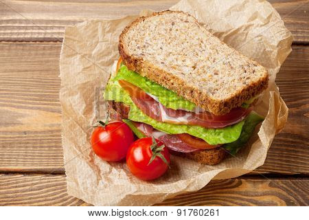 Sandwich with salad, ham, cheese and tomatoes on wooden table