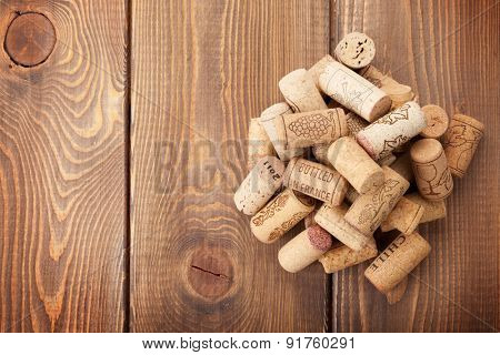 Wine corks heap over rustic wooden table background. Top view with copy space