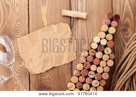 Wine bottle shaped corks, wine glass and corkscrew over rustic wooden table background. Top view with copy space