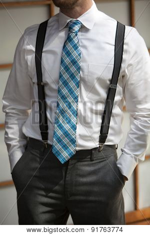 Young Man Wearing Suspenders And Colorful Tie With Hands In Pockets.