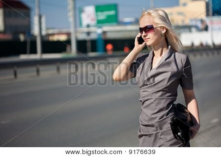 Woman In Grey Dress Walking And Calling By Phone