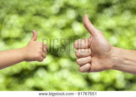 Father And Son Hands Giving Like On green Background