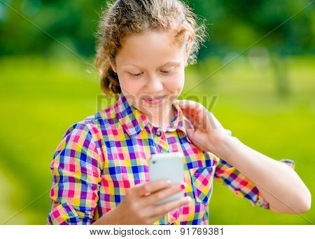 Adorable Smiling Teenage Girl In Casual Clothes With Smartphone In Her Hand, Looking At Screen