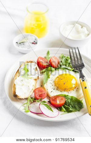 Fried Egg With Tomatoes, Arugula, Radish, And Toast With Cheese On A Light Surface