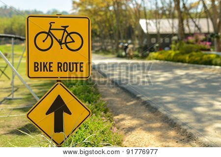 A Yellow Bike Route Sign On The Side Of The Road.