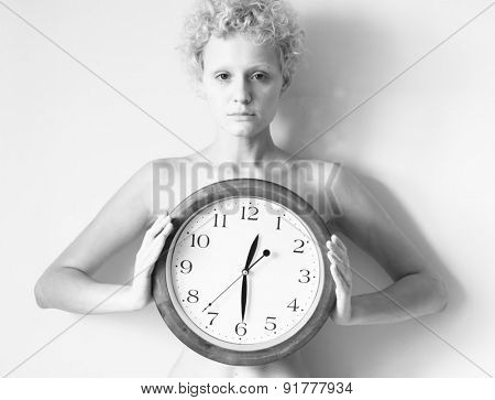 Sensitive curly girl with big clock in hands. Black and white photo.