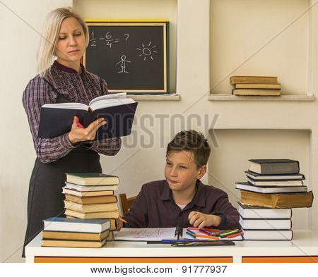 Elementary school student doing homework with the help of a tutor.