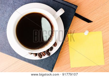 Coffee And Note Pad On Wood Desk Table