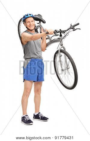 Full length portrait of an active senior biker carrying his bicycle over his shoulder and looking at the camera isolated on white background