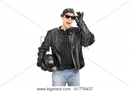 Young biker with sunglasses and leather jacket looking at the camera and smiling isolated on white background