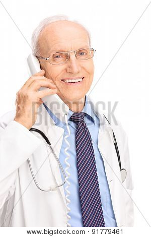 Vertical shot of a mature doctor speaking on a telephone and smiling isolated on white background