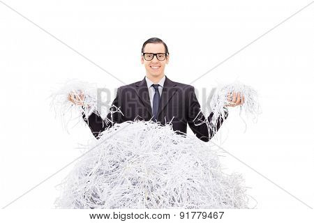 Cheerful businessman holding shredded paper in both hands and smiling isolated on white background