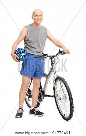 Full length portrait of an active elderly man holding a blue sports helmet and posing next to a bicycle isolated on white background