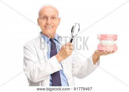 Joyful mature dentist holding a denture and a magnifying glass and looking at the camera isolated on white background