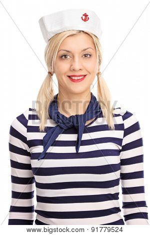Vertical studio shot of a female sailor wearing a striped white and blue shirt and a sailor hat looking at the camera and smiling isolated on white background