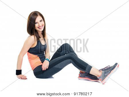 Cheerful sporty woman sitting on the floor isolated on a white background. Looking at camera