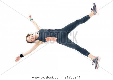 Beautiful happy fitness woman lying on the floor isolated on a white backgroun. Looking at camera