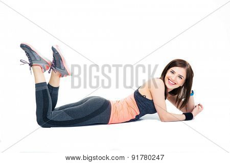Smiling sporty woman lying on the floor isolated on a white background and looking at camera
