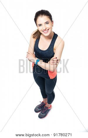 Full length portrait of a happy sporty woman standing with arms folded isolated on a white background