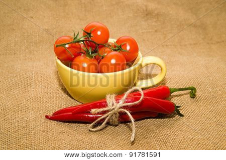 Red Cherry Tomatoes In A Yellow Cup And Chile Peppers  On Old Cloth