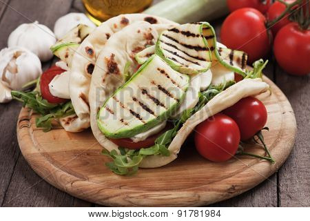 Piadina romagnola, italian flatbread sandwich with rocket salad, mozzarella cheese and grilled zucchini