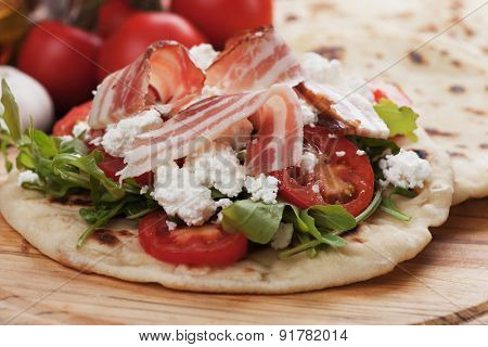 Piadina romagnola, italian flatbread sandwich with rocket salad, mozzarella cheese and pancetta bacon