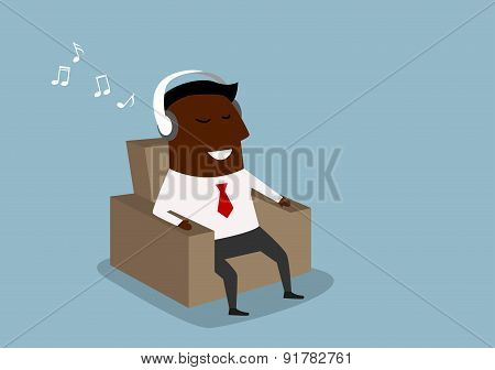 Black businessman listening to music on headphones