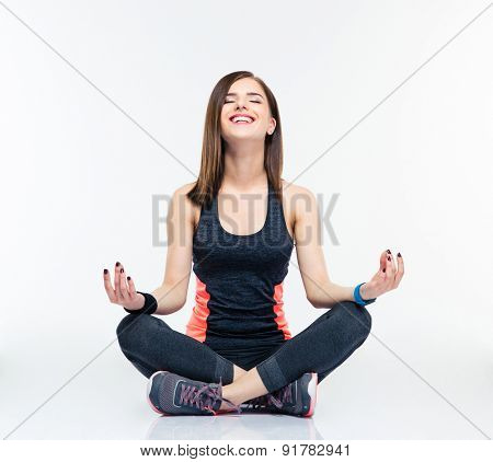 Happy fitness woman meditating isolated on a white background