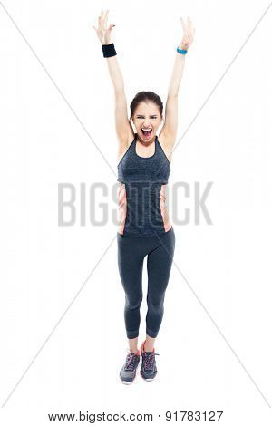 Full length portrait of a happy sporty woman standing with raised hands up isolated on a white background. Looking at camera