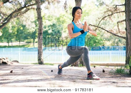 Young sporty woman stretching and meditating outdoors in park