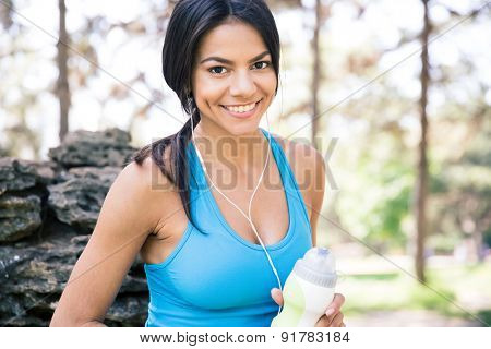 Smiling sporty woman outdoors holding bottle of water outdoors in park
